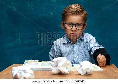 Angry child sitting at workplace imitating businessperson or office worker. Stylish boy sitting at workplace with crumpled papers and documents.