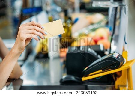 partial view of shop assistant holding credit card in hand at cash point in supermarket