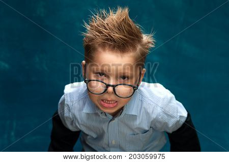Portrait of crazy businessman child or office worker. Little boy wearing eyeglasses and shirt with tousled hair posing on blue backdrop