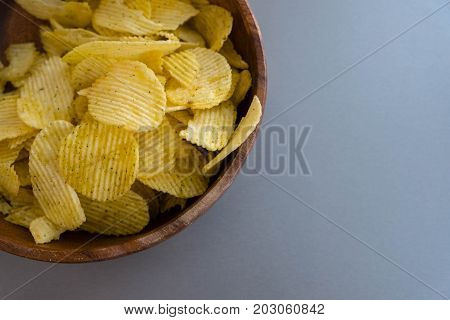 Potato chips in bowl on a grey background top view. Salty crisps scattered on a table