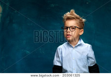 Funny portrait of caucasian child wearing eyeglasses and shirt imitating businessperson or office worker. Little boy posing on blue backdrop. Blurred image, Copyspace