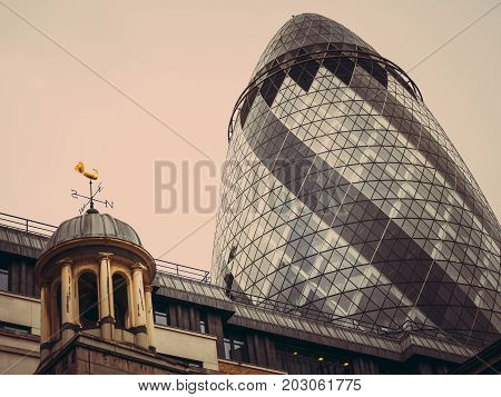 LONDON, UNITED KINGDOM - March 19, 2017: City of London. Modern and old architecture. The Gherkin building tower over the old buildings in the financial district of London. On a cloudy day in March