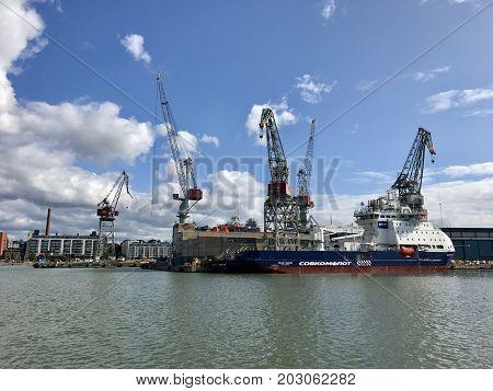 HELSINKI - SEPTEMBER 6, 2017: A cargo ship and loading cranes in the port of Helsinki, Finland.