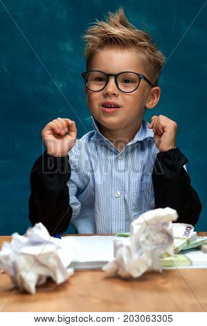 Cute stylish boy wearing eyeglasses sitting at workplace with cash and crumpled papers. Portrait of child imitating businessperson or bookkeeper.