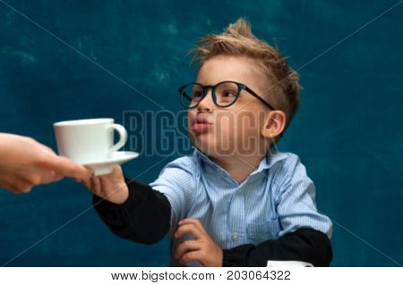 Portrait of stylish business child wearing eyeglasses sitting at workplace, having break with cup of drink. Cute caucasian boy imitating businessperson or office worker. Blurred image