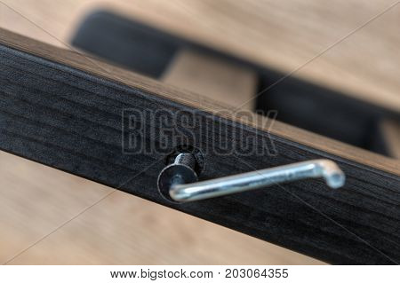 Screwed up furniture screw in wooden plank with allen key build a wooden chair at home.