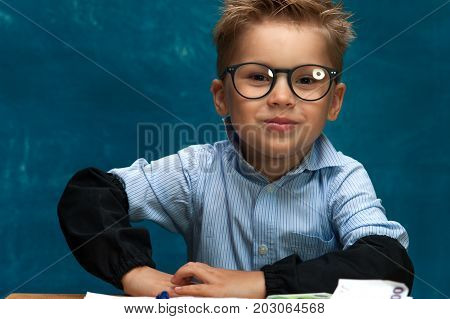 Smiling cheerful boy wearing eyeglasses and shirt posing on blue backdrop. Little child imitating businessperson or office worker at workplace.