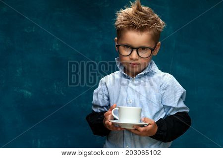 Cute caucasian child wearing eyeglasses posing with cup of drink. Little boy imitating businessperson or office worker having a break.