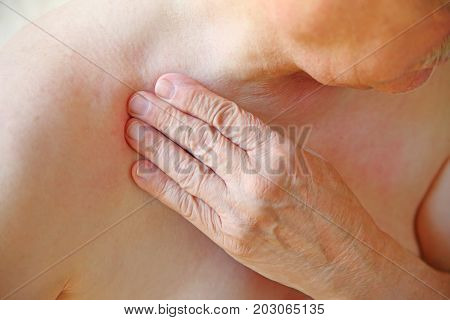 An older man with his hand on an area near his shoulder