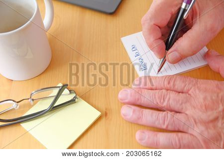 A man with a pen glasses note pads and coffee cup on a desk