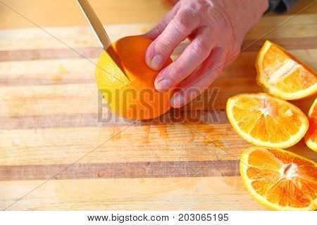 A man cuts up blood oranges on a cutting board with room for text