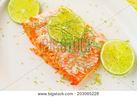 Portion of roasted salmon with lime slices and fresh dill on a white platter with room for text