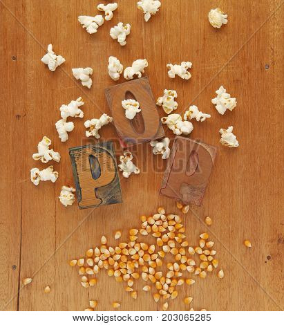 The word pop in wood letters with both unpopped and popped kernels of corn on a wood surface