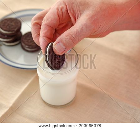 A man dips a cookie in a glass of milk with copy space