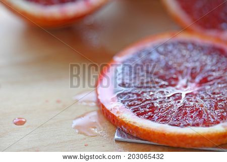 Closeup of a fresh slice of blood orange on a cutting board