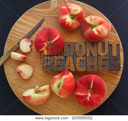 Fresh donut peaches whole and with pieces cut with words in wood type and a kitchen knife on a cutting board