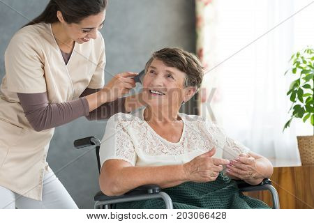 Volunteer Brushing Pensioner's Hair