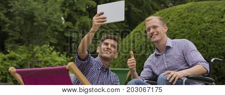Friends making common selfie using the tablet