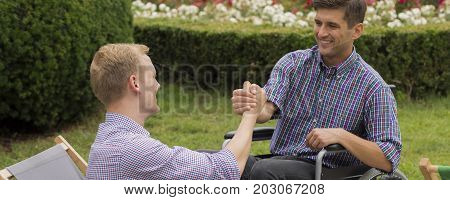 Handshake between two smiling friends in the park