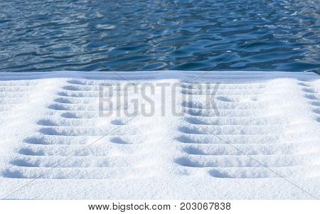 Pier in snowdrifts. Lake Shore. Selective focus.