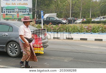 THAILAND--A woman sells flower leis to vehicles at a traffic light in one of the roads to the northern part of Thailand. Photo taken in March 2016.