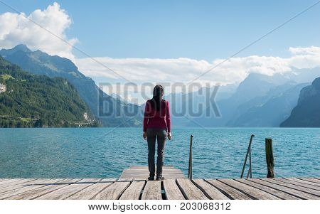 Woman with long hair standing on the shore of the lake. Mountain range in the background.