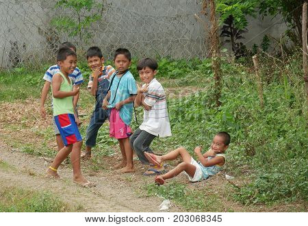 DAVAO ORIENTAL, PHILIPPINES--MARCH 2016: A group of happy boys posting for the camera at the side of the road in Davao Oriental, southern Philippines.