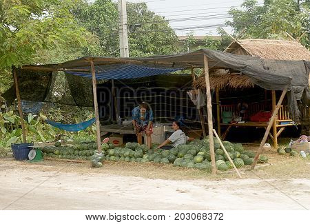 THAILAND--MARCH 2016: A female vendor sells watermelon fruit from a makeshift tent alogn the highway to the northern part of Thailand.