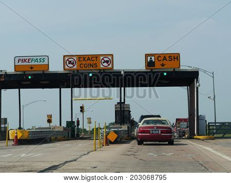 LAWTON, OKLAHOMA--Cars passing through a toll highway station heading to Lawton, Oklahoma is September 2015.