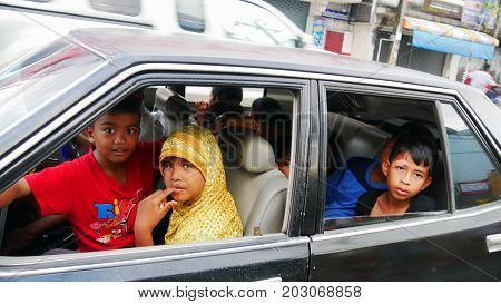 NARATHIWAT, THAILAND--Photo of seven excited children plus the driver all squeezed into one car in Narathiwat, Thailand in March 2016.