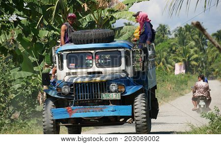 DAVAO ORIENTAL, PHILIPINES--A blue truck with passengers kicks off dust as it travels along the roads by the ricefields in Banay-banay, Davao Oriental in March 2016.