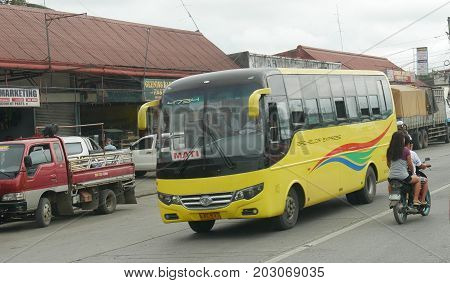COMVAL PROVINCE, PHILIPPINES--A yellow Bachelor Express heading out of Pantucan Transport Terminal in Compostela Valley Province, heading to Mati, Philippines in March 2016.