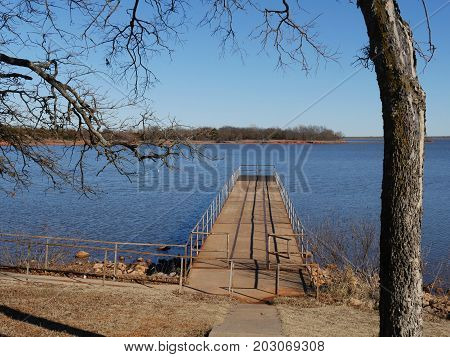 Wooden dock and lookout with railings over the blue waters of Thunderbird Lake State park on a cold day