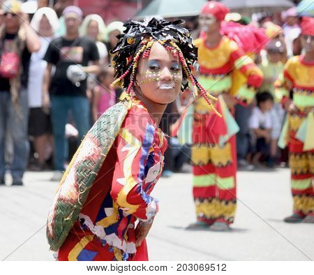 DAVAO CITY, PHILIPPINES--AUGUST 2014: A girl with painted face and colorful headdress dancing at the streets. Kadayawan is celebrated August each year to give thanks for life and an abundant harvest.