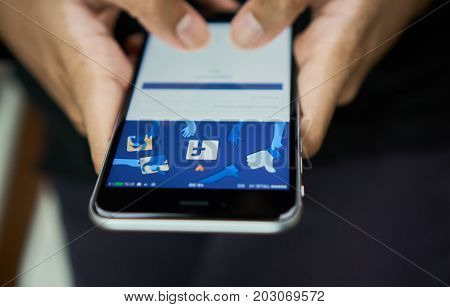 Bangkok Thailand - September 6, 2017 : hand is pressing the Facebook screen on apple iphone6 Social media are used for information sharing and networking.