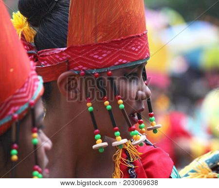 DAVAO CITY, PHILIPPINES--AUGUST 2014: Close up shot of a girl with colorful headdress and beads at the parade.  Kadayawan is celebrated August each year to give thanks for an abundant harvest. Davao,