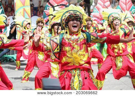 DAVAO CITY, PHILIPPINES--AUGUST 2014: Participating teams giving their best in performance at the streets. Kadayawan is celebrated August each year to give thanks for life and an abundant harvest.