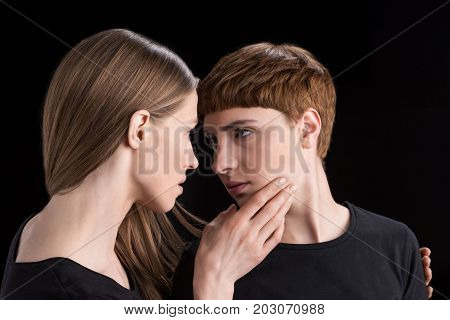 Young Woman Holding Girlfriend By Chin