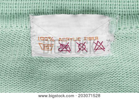 Fabric composition and washing instructions clothes label on cyan knitted background