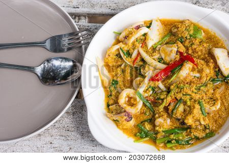 Fried Squid curry powder.Fried crab in yellow curry on white plate. Stir-fried crab curry.food in beach concept.Beach restaurant