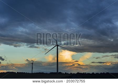 Wind Turbines For Electrical Power Generation In Green Fields On A Cloudy Day In Normandy, France. R