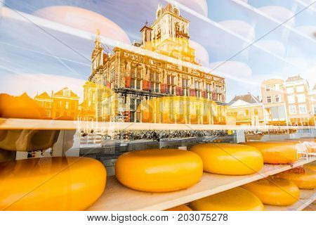 Dutch cheese heads on the shelves of the showcase with reflection of Delft city in Netherlands
