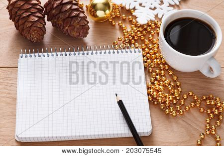Christmas planning background. Prepare to winter holidays. Top view flat lay of xmas decorations, note papers, pen and coffee on wood. Copy space for wishlist or shedule