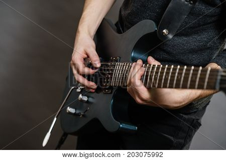 Male hands with electric guitar. Close up part body adult person is holding instrument and playing. Hobby music concept