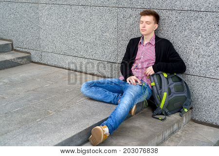 Quiet serene young man in plaid shirt and jeans listening to music with headphones from cell phone outdoors. Student with closed eyes sitting with smart phone and headphones at stone wall