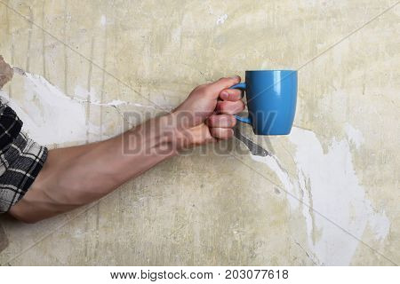 Male Hand Holding Cup On Brick And Textured Background