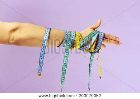 Hand With Flexible Rulers On Light Purple Background