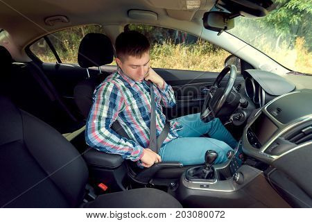 Handsome Serious Young Man In Plaid Shirt Fastening Seat Belt In Car. Businessman Putting On His Sea