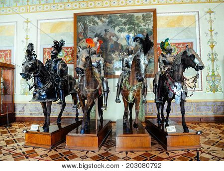Saint Petersburg, Russia - April 14, 2017 - Mannequins of ancient knights in armor on horses in Hermitage museum with murals on background. Riding, hero, medieval warriors, historic landmarks, castle.