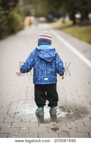 Autumn. Baby stands in a puddle on the road